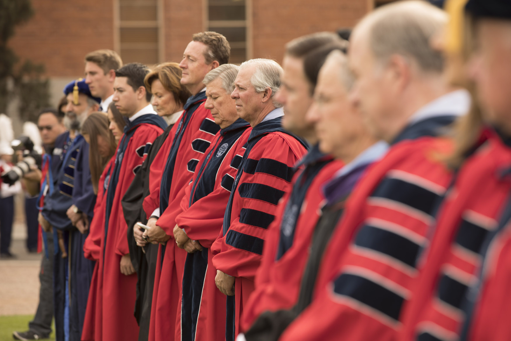 Platform Party and processing faculty stand at attention